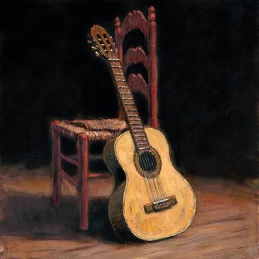 Guitarra flamenca apoyada sobre una silla